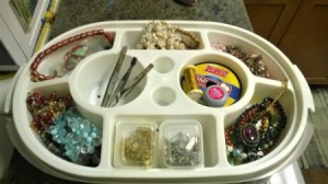 An old Tupperware container with several sections filled with jewelry findings.