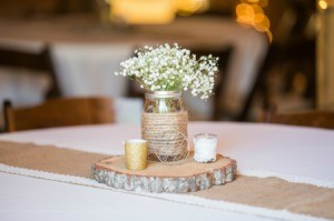 Mason jar wrapped with Jute rope filled with Babies Breath flowers on a table.