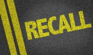 The word Recall painted in yellow on a street.