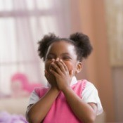 Cute little girl covering her mouth while laughing.