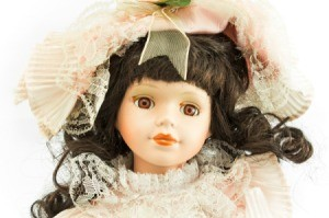 Porcelain Doll with brown curly hair.