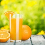 Glass of orange juice and a orange cut in half.