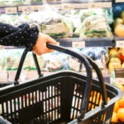 Person holding a shopping basket in font of the produce section.