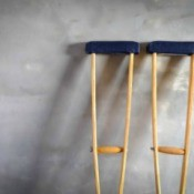 Pair of crutches up against a cement wall.