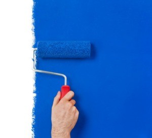 Paint roller painting a white wall blue.