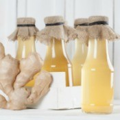 Ginger Syrup in bottles with piece of ginger.