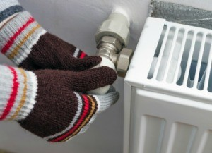 Gloved hands adjusting thermostat