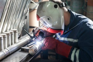 Man welding pipes together