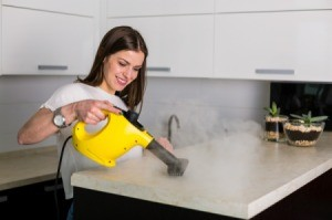Woman using steamer to clean countertop