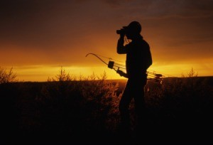 Man out bow hunting at down