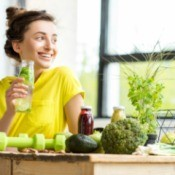 Woman drinking water at table with healthy foods
