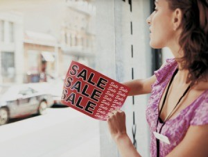 Woman removing sale decal from window