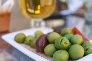 Plate of spiced olives with glass of white wine in background