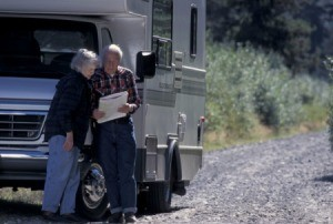 Elderly couple outside their RV looking at a map