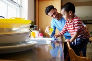 Father helping his son washing dishes