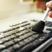 Using make-up brush to clean computer keyboard