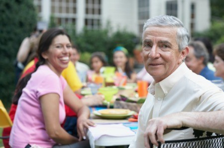 Man at his Retirement Luncheon with woman smiling in background