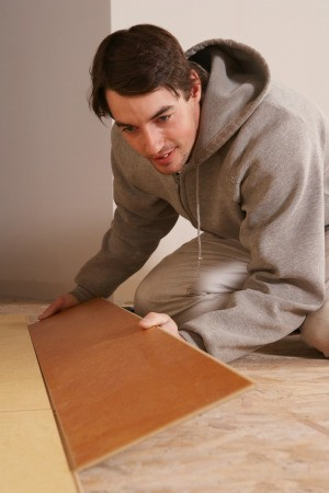 A man installing flooring on particle board.