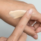 A hand testing the tone of a tinted moisturizer.