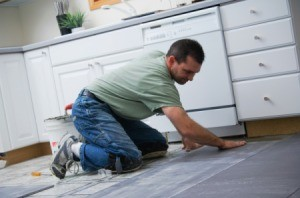 Man laying tile in a kitchen.