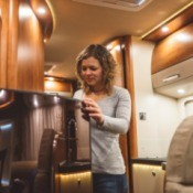 Woman opening a fridge in a RV.