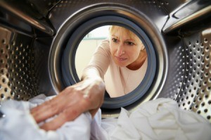 Woman reaching into a dryer.