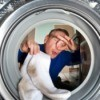 Man holding his nose putting smelly socks in the washing machine