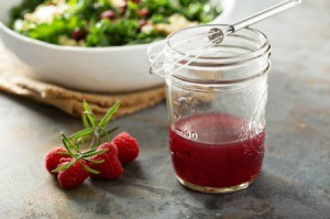 Raspberry Vinaigrette in mason jar with whisk, fresh raspberries and a salad