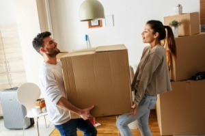 Couple carrying heavy box they have packed to move out