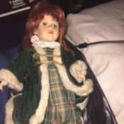 Identifying a Porcelain Doll - doll wearing a plaid dress and green long fur trimmed coat
