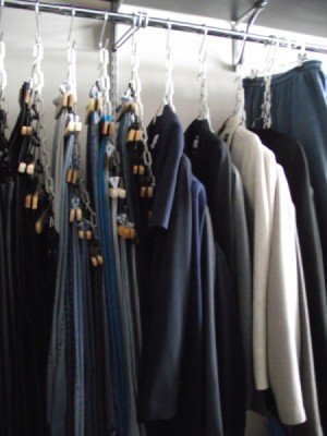 Clothes hanging from chains in the closet.
