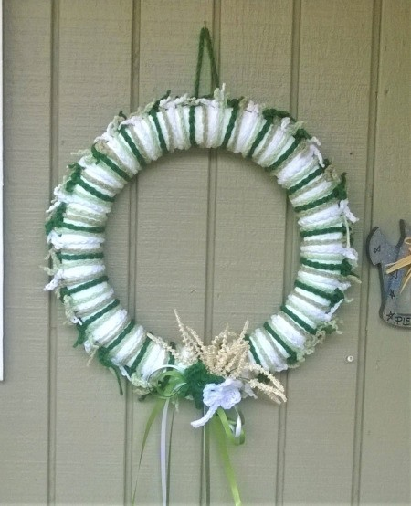 Yarn Chain St. Patty's Wreath - finished wreath hanging on an exterior wall