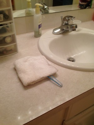 A toothbrush under a folded white washcloth.