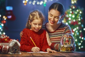 Mom and daughter writing a letter near the Christmas tree.