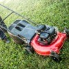 Man pushing red lawn mower on grass