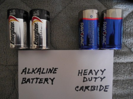A set of alkaline batteries next to a set of heavy duty carbide batteries.