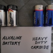 A set of alkaline batteries next to a set of heavy duty carbide batteries.