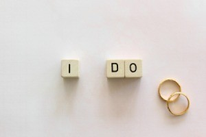 "Three small blocks spelling ""I Do"" next to two rings."