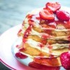 Stack of pancakes with strawberry syrup.