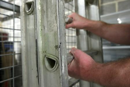 Hands putting a ladder away.