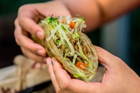 A person holding a taco, ready to eat.