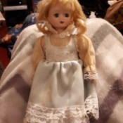 Identifying a Porcelain Doll - blond doll with white pinafore over pinkish blouse