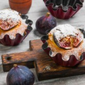 Fig muffins with fresh figs on the table next to them.