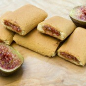 Fig cookies next to a fig sliced in half.