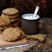 Oatmeal cookies next to a cup of cocoa.