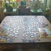 A jigsaw puzzle being worked on a card table.
