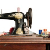 Antique sewing machine on a sewing table with thread.