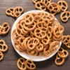 A batch of small pretzels in a white bowl.