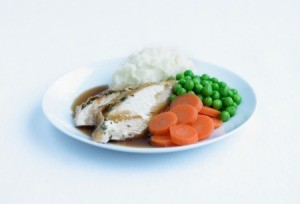 Roast chicken dinner with carrots, pees, and mashed potatoes on a white plate.