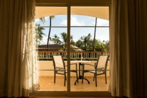 Looking through a sliding glass door to a balcony in a tropical place.